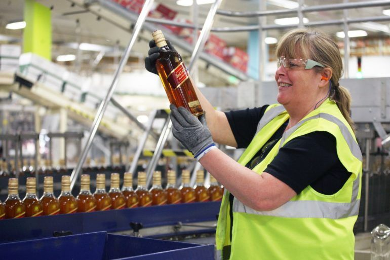 Woman examining the quality of the whisky on the bottling line at Diageo, Renfrew