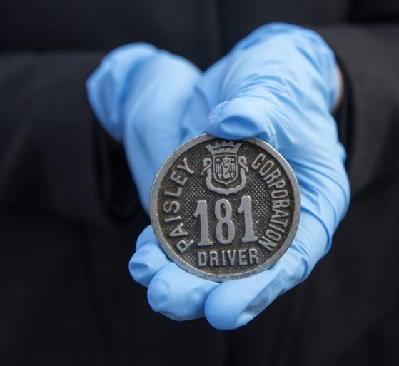 Close up of a pair of hands wearing blue gloves holding an item from the secret collection, a Paisley Corporation Driver badge number 181