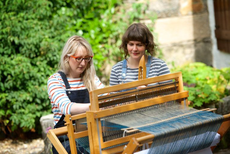 Two weavers at a loom
