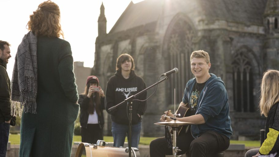 Student busker playing drums outside Paisley Abbey