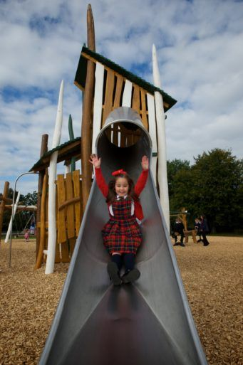 Girl slides down chute at opening of new playpark in Barshaw Park