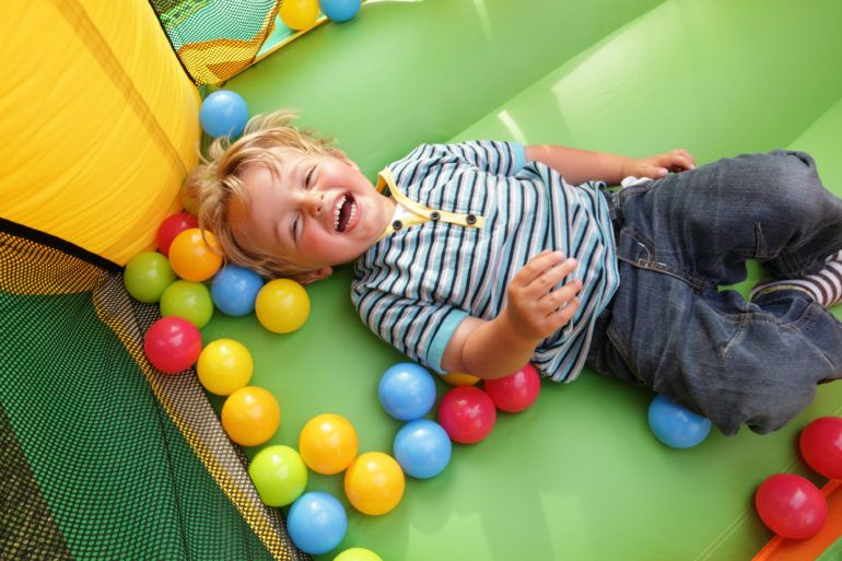 Child having fun in bouncy ball pit play area