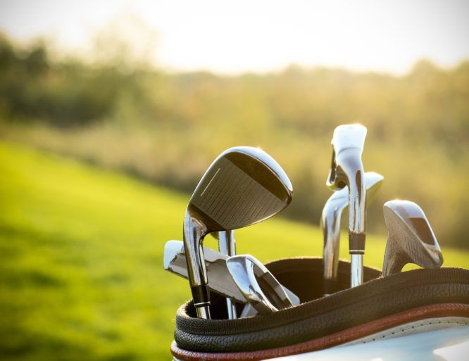 Close up of gold clubs over green field background. Summer sunset