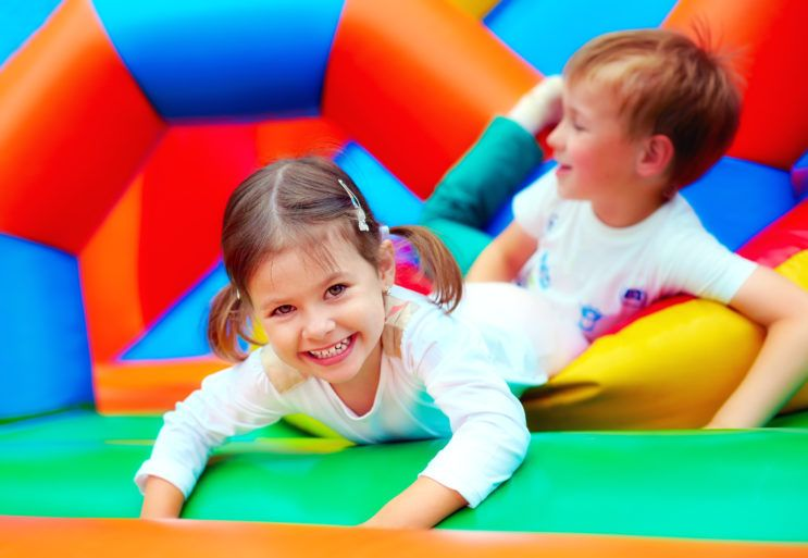 Kids playing on bouncy castle at soft play