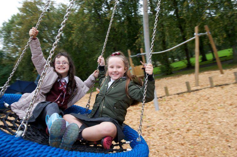 Girls playing on swings at Robertson Park, Renfrew