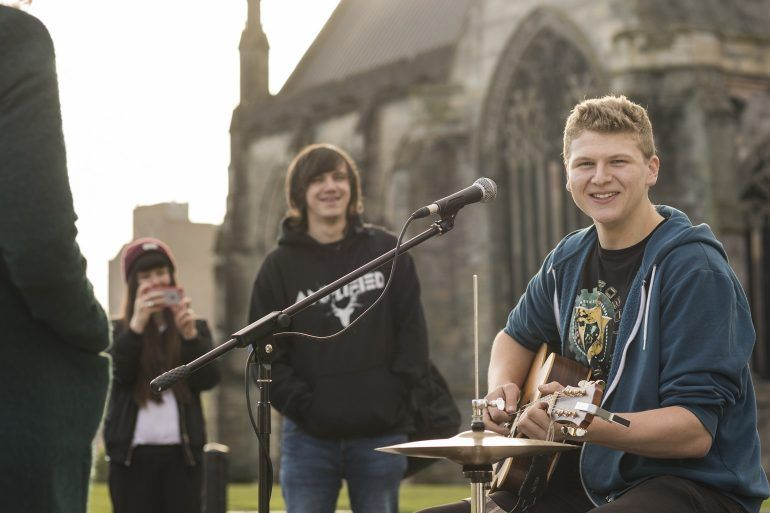 Paisley Is campaign image - Drummer busks outside Abbey