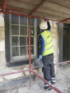 Worker repointing at Sma' Shot Cottages